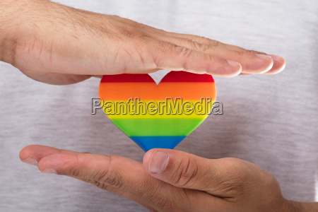 man holding rainbow lgbt heart