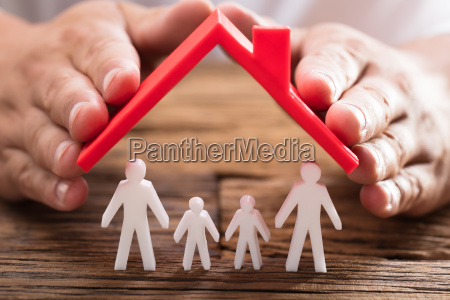 person protecting family figures with roof