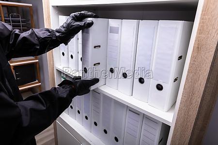 thief stealing folder from shelf