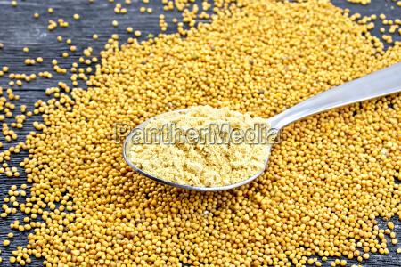 mustard powder in spoon on board
