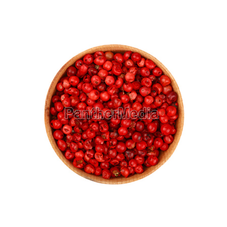 wooden bowl full of pink peppercorns