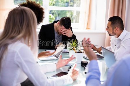 businesspeople blaming their colleague in office