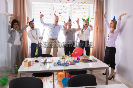 group of businesspeople celebrating in office