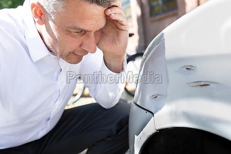 man looking at damaged car