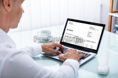 businessman looking at invoice on laptop