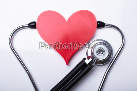 examining red heart with stethoscope