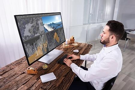 man editing 3d landscape on computer