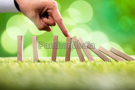 person stopping falling wooden blocks