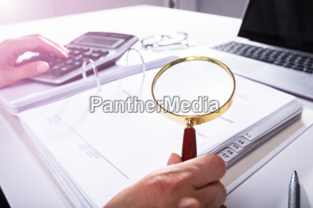 businessperson analyzing bill with magnifying glass