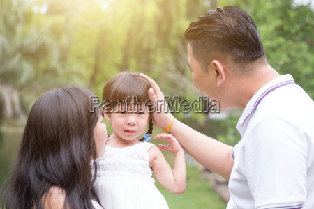 parents comfort crying daughter