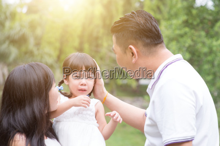 parents comfort crying daughter outdoors