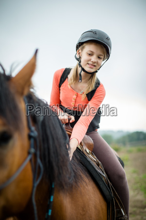 cute young girl riding a horse