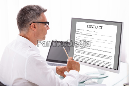 businessman reading contract on computer