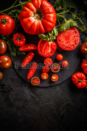 cutting red tomatoes composition