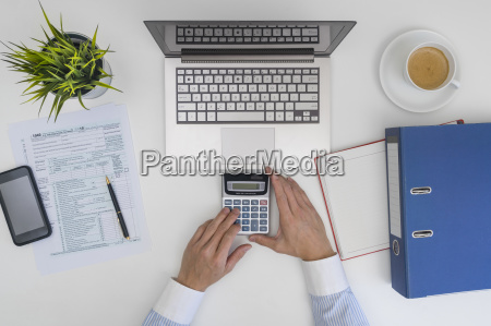 businessman making calculation and filling tax