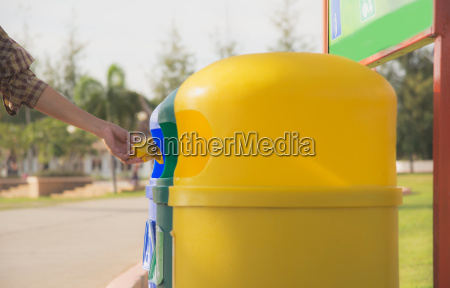 blue and yellow plastic trashcan in