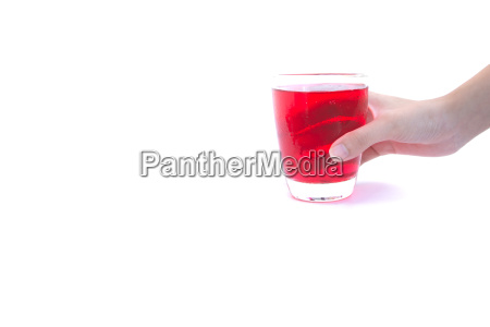 hand holding a glass of syrup