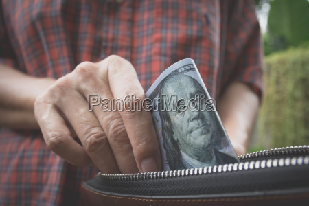 male holding banknote in wallet in