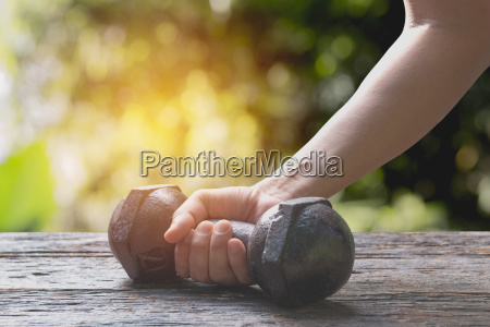 hand of person holding dumbbell for
