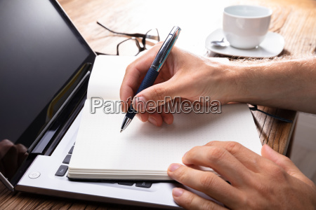 persons hand writing on black notebook