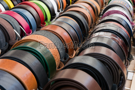 different leather belts at a market