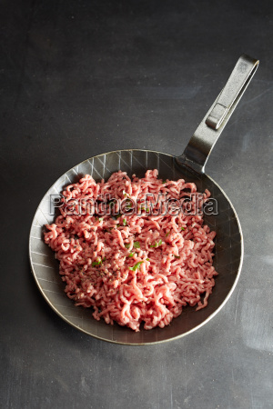 pan with minced meat against black