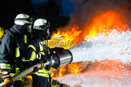 firefighter firemen extinguishing a large