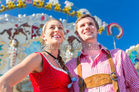 couple visiting bavarian fair having fun