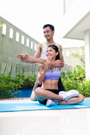 asian woman with trainer at fitness