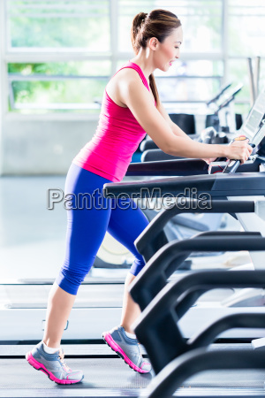 sportive girl doing workout on treadmill