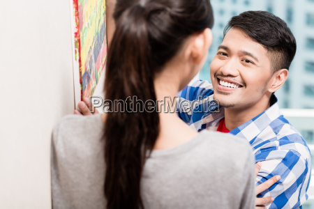 young asian couple hanging up picture