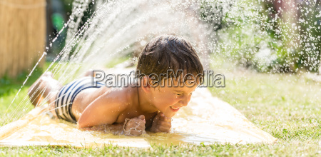 boy cooling down with garden hose