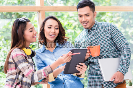 three cheerful young employees working together