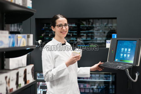pharmacist using a computer while managing