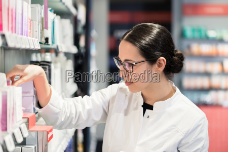 pharmacist standing in front of various