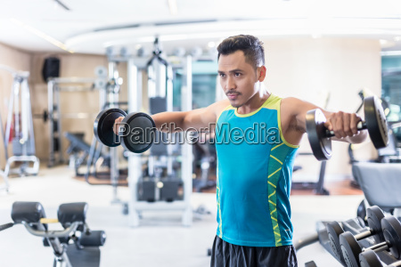 handsome determined young man exercising with
