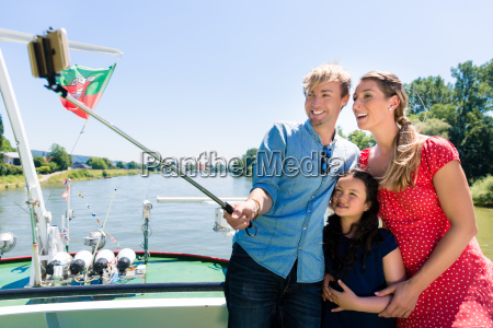family on river cruise with selfie