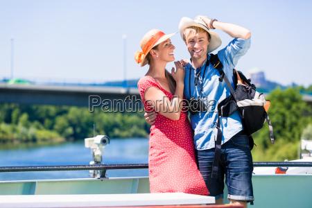 couple on river cruise wearing sun
