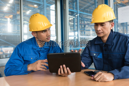two asian workers analyzing information indoors