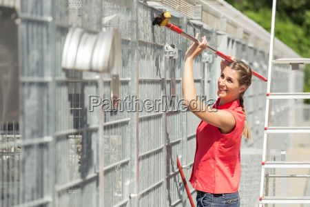 zookeeper woman working on cleaning cage