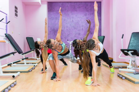 fit women exercising with one arm