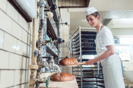 baker woman getting bread out of
