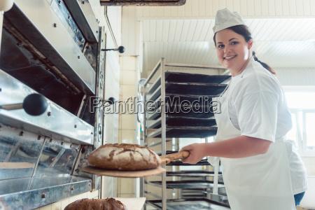 baker getting fresh bread with shovel