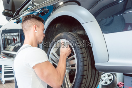 skilled auto mechanic replacing the rims