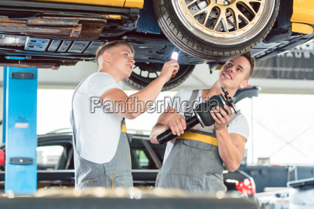 two auto mechanics analyzing the rims