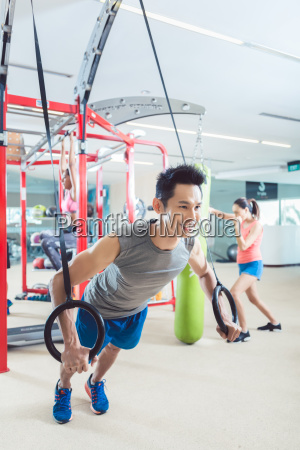 fit young man exercising with gymnastic
