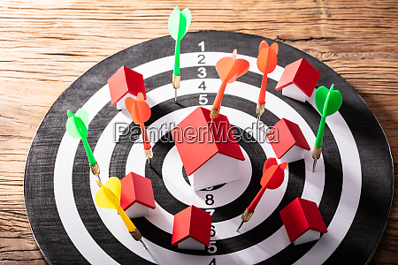 colorful dart arrows hitting house model