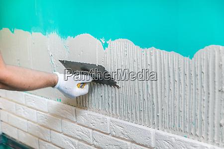 tiler applying tile adhesive on the