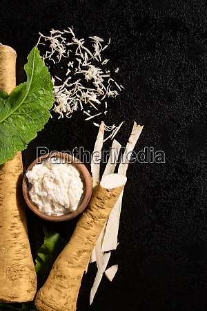 fresh grated horseradish roots on black