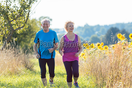 cheerful senior couple jogging together outdoors